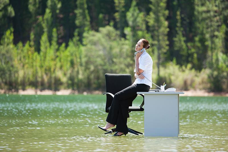 femme sur un bureau les pieds dans l'eau